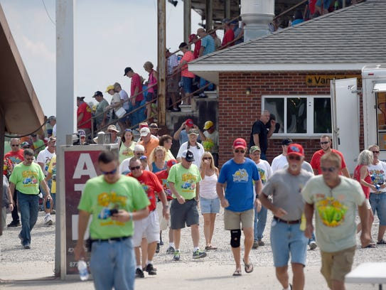 Hot rod owners and fans exit the grandstand while attending