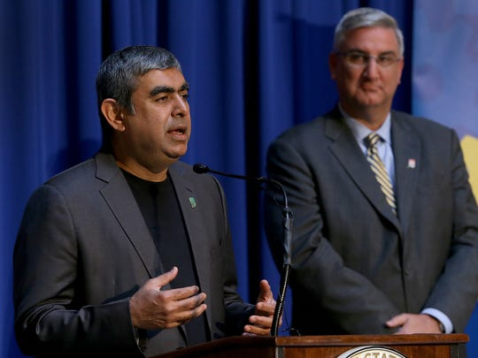 Infosys CEO Dr. Vishal Sikka announces his company to bring 2000, high-skilled high tech to central Indiana by the end of 2021. Indiana Governor Eric Holcomb,right, listens to the announcement Tuesday. May 2, 2017, at the Indiana Statehouse.
