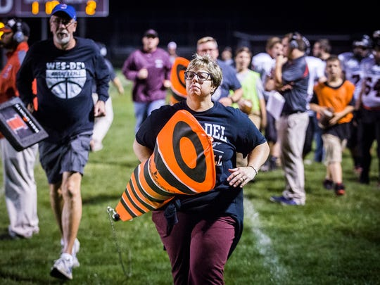 Amy Cullum, a teacher at Wes-Del High School and the mother of Alex Cullum, volunteers on the chain gang during Wes-Del's game against Edinburgh.