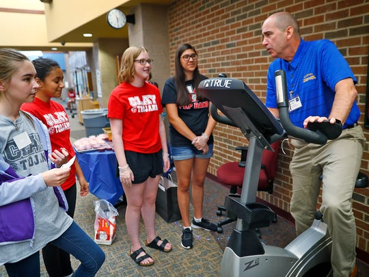 "New Superintendent of Carmel Clay Schools Michael Beresford, right, talks with students while riding an exercise bike to ""earn"" a smoothie drink, at an activity station at the #C4: Connect, Collect, Collaborate, and Create conference, held at Clay Middle School, Wednesday, July 11, 2018."