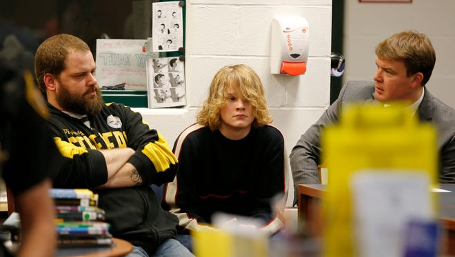 Madison student Cooper Caffrey and his father Marty (left) react as the board unanimously approves the arming of educators during a meeting of the school board at Madison Jr./Sr. High School in Madison Twp., Ohio, on Tuesday, April 24, 2018. Caffrey along with more than 40 other students were punished for participating in a planned walkout to protest gun violence. Cooper was shot during a school shooting in 2016.