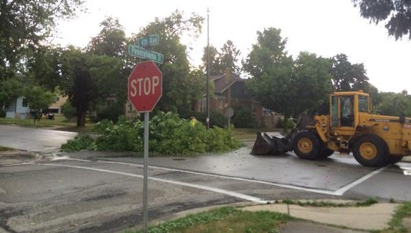 Crews clear downed tree branches from a street in Sturgeon Bay.
