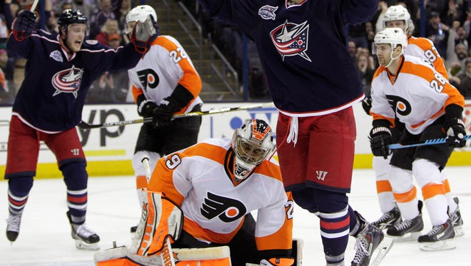 Columbus Blue Jackets' Artem Anisimov, right, of Russia, celebrates his game-winning goal against the Philadelphia Flyers during overtime.
