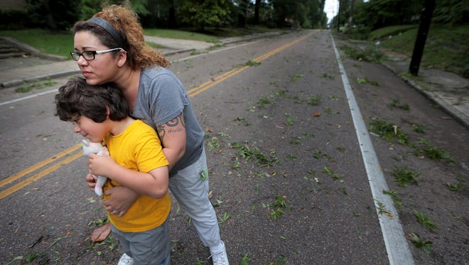 Mclean residents Kim Davis and Parker Davis, 6, watch as neighbors try to make a path through a knot of trees and power poles blocking blocking the street after a severe thunderstorm knocked out power to most of Memphis Saturday night