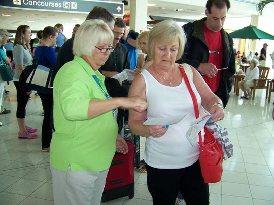 Lee County Visitor Services volunteer Linda Rossi, left, helps travelers make sure they are in the correct concourse line during a peak time at  Southwest Florida International Airport on Wednesday, March 16, 2016.
