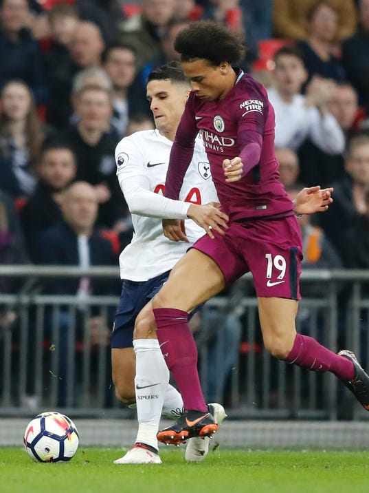 Tottenham's Erik Lamela, left, battles for the ball with Manchester City's Leroy Sane during the English Premier League soccer match between Tottenham Hotspur and Manchester City at Wembley stadium in London, England, Saturday, April 14, 2018. (AP Photo/Frank Augstein)