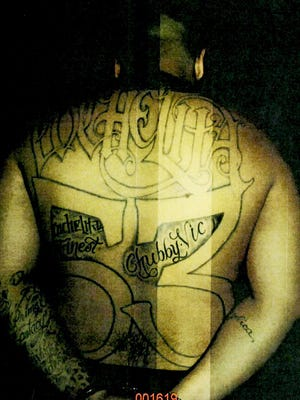 Angel Servina, a confirmed gang member, is photographed during an assault arrest in 2011.