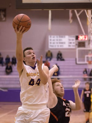 Kirtland Central's Bryson Dowdy scores over Aztec's Chase Morrison on Thursday at Bronco Arena in Kirtland.