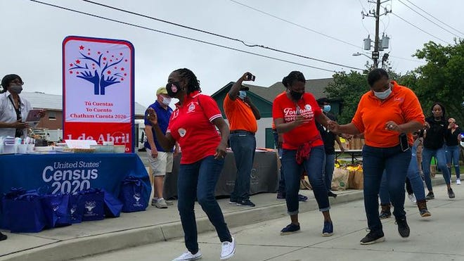 Volunteers dance at Saturday's census outreach event on Waters Avenue, where everyone was welcome to collect free food and school supplies while filling out their census forms.