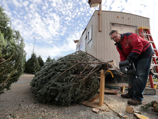 Bruce Lembcke, a member of the Y-Service Club, trims the base of a Christmas tree for a customer on Friday at the YMCA Christmas tree lot in the parking lot at Festival Foods in Appleton.