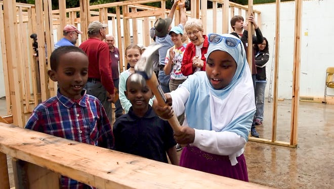 Nimo Mohamud, 9, hammers a nail into her families new home being built by the Central Minnesota Habitat for Humanity Build for Unity project Wednesday, June 28, in Sauk Rapids.