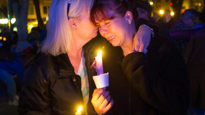 Tonya Castillo (left) comforts her daughter Tiffany Reid during a candlelight vigil for Kayla Mueller in Prescott February 18, 2015. Reid and Mueller were friends.