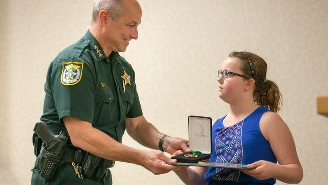 Chief deputy of operations Chip Simmons hands a civilian service medal to ten-year-old Morgan Boutwell during an award ceremony at the Escambia County Sheriff Office in Pensacola on Thursday, March 23, 2017.  Boutwell is being recognized for her swift action that saved the life of her two-year-old cousin who was drowning.