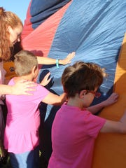 NMSBVI teacher Dana Hollederer assists students Ivory Willburn and Mandy Blaes as they feel the hot air balloon inflate.