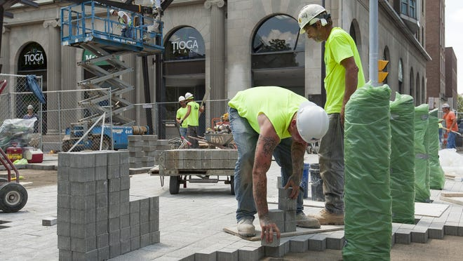 The crew from contractor Syrstone installs the last pavers where the Commons meets Seneca Street at the north end of Bank Alley Wednesday afternoon.