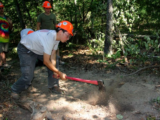 Nixa scout Robert Lyford wields an axe against stubbord tree routes in the middle of the future mountain biking trail at Camp Arrowhead