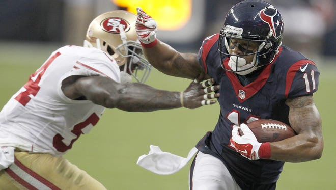 HOUSTON, TX- AUGUST 28: DeVier Posey #11 of the Houston Texans stiff arms Asante Cleveland #45 of the San Francisco 49ers in the first quarter in a pre-season NFL game on August 28, 2014 at NRG Stadium in Houston, Texas. (Photo by Thomas B. Shea/Getty Images)