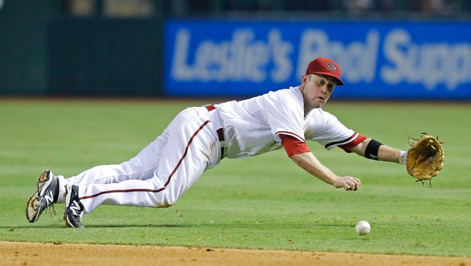 Arizona Diamondbacks second baseman Aaron Hill (2) makes a diving stop for an out to preserve their win in the 9th inning of their MLB game against he Detroit Tigers at Chase Field Tuesday, July 22, 2014 in Phoenix, Ariz.