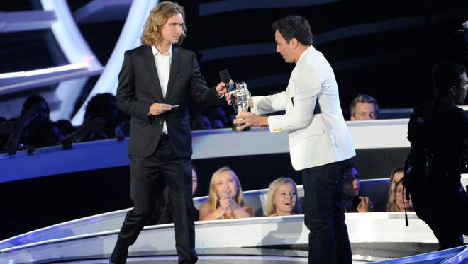Jesse Helt, a homeless man, left, accepts the award for Video of the Year from Jimmy Fallon on behalf of Miley Cyrus on stage at the MTV Video Music Awards in Inglewood, California on Aug. 24, 2014. Helt arrived 45 minutes late for his arraignment Tuesday, Sept. 16, on a charge that he violated his probation in Oregon. He gained worldwide attention last month when Cyrus let him accept her award for video of the year. It was later learned that Helt was wanted in Oregon for a probation violation stemming from a 2010 arrest.