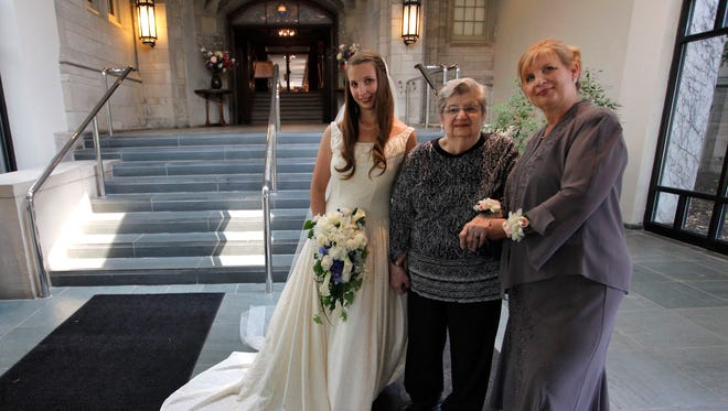 Cristin Seeley-Coleman, left, poses at the Memorial Art Gallery Friday with her grandmother, Jean Wydysh Chappell, center, and her mother, JoAnne Chappell Seeley. The event marks the third generation wearing Chappell's silk wedding dress from 1947.