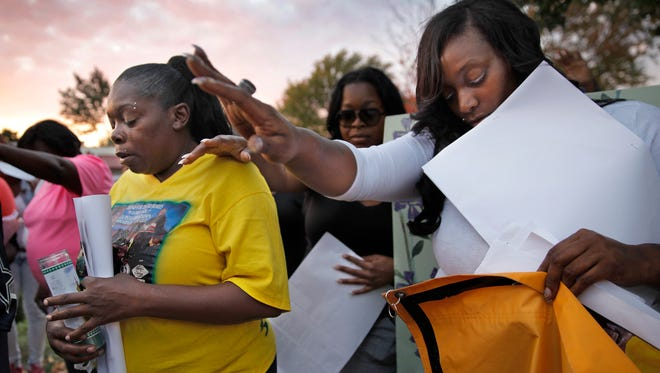 Charnette Grayson, left, and Pamela Smith, right, pray with a group at the corner of Driving Park and Dewey Ave where Latasha Shaw was murdered seven years ago after a march of remembrance organized by Coalition of Black Trade Unionists of which Shaw was a member.  Grayson is Shaw's sister and Smith is her cousin and worked with her.