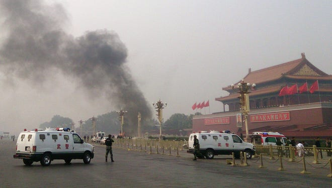 Police cars block off the roads leading into Tiananmen Square as smoke rises into the air after a vehicle crashed in front of Tiananmen Gate in Beijing. Three people were killed when an SUV vehicle crashed into a crowd in Beijing's Tiananmen Square and burst into flames, state media said.