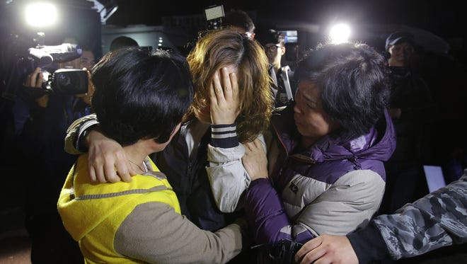 Relatives weep as they wait for missing passengers of a sunken ferry at Jindo port on April 16, 2014 in Jindo-gun, South Korea.   The ferry Sewol's passengers included high school students and teachers.