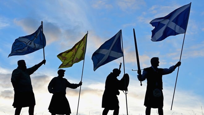 Duncan Thomson, Brian McCutcheon, John Patterson and Arthur Murdoch, from King of Scots Robert the Bruce Society, hold the Scottish flags Sept. 14,  in Loch Lomond.