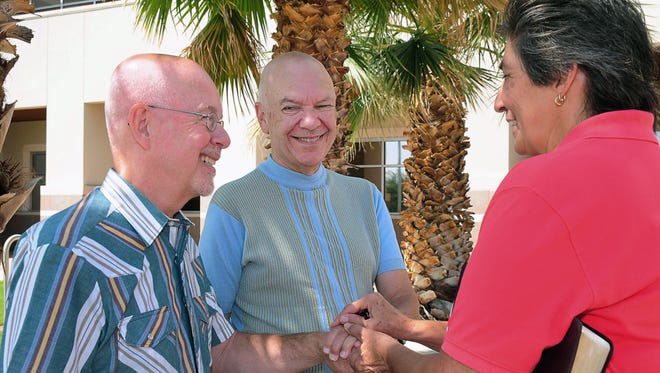 Richard Sunman, left, and Thom Hinks of Albuquerque, N.M. have their wedding rings blessed by Rev. Vangie Chavez, of the Rising Sun Christian Community in Las Cruces, N.M. on Thursday.