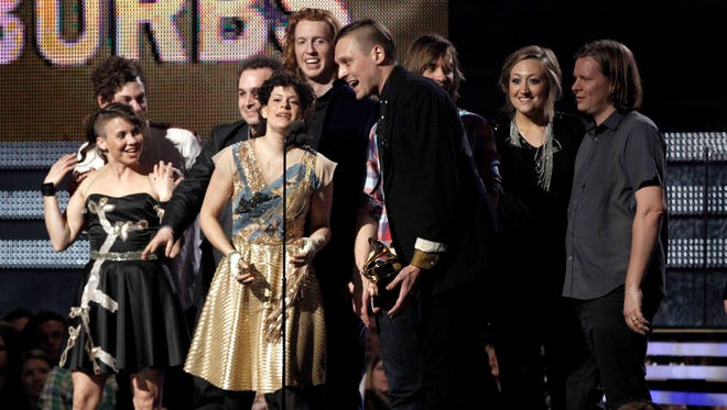 Regine Chassagne, center left, and Win Butler, center right, are joined by fellow band members of Arcade Fire to accept the award for album of the year at the Grammy Awards in February 2011 in Los Angeles.