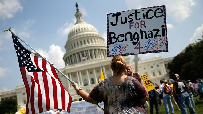"""Jennifer Brandt holds signs during a """"Call to Action"""" rally held by various conservative organizations on the grounds of the U.S. Capitol on Sept. 11, marking the one-year anniversary of the attack on the U.S. compound in Benghazi, Libya."""