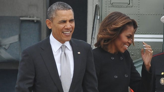 President Obama and First Lady Michelle Obama, shown in a March file photo, saw their income drop significantly last year.