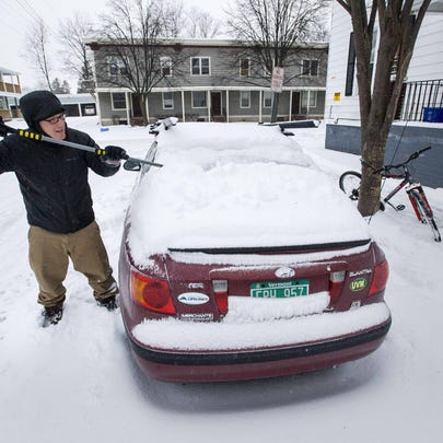 Jon Ayers clears snow from his car on  Clarke Street
