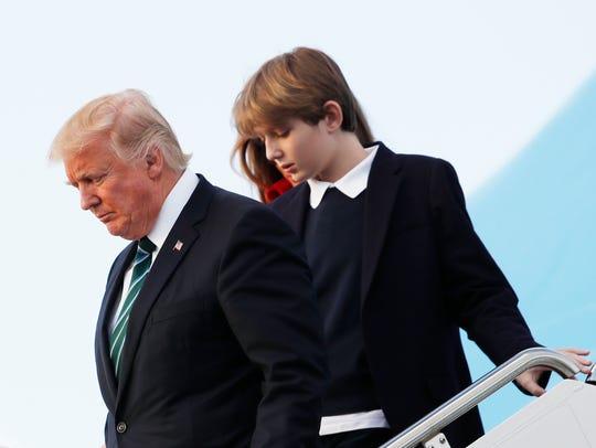 Barron Trump with father President Trump disembark