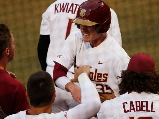 Florida State's Carter Smith celebrates with teammates after scoring a run against Georgia during an NCAA college baseball tournament regional game Saturday, June 1.