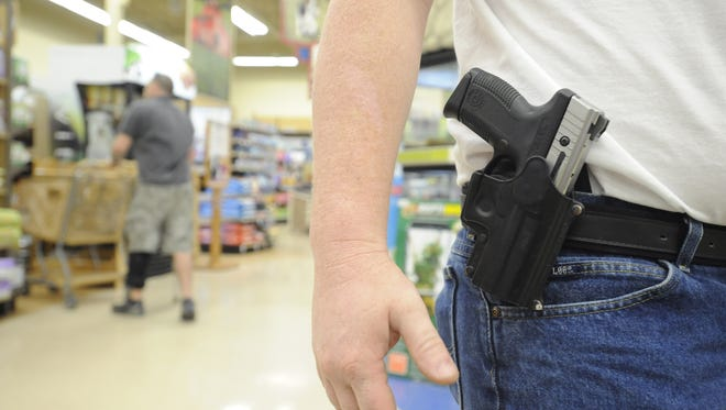 Brian Morrison, of Mountain Home, Ark., carries a firearm Tuesday while shopping at a pet store in Mountain Home.