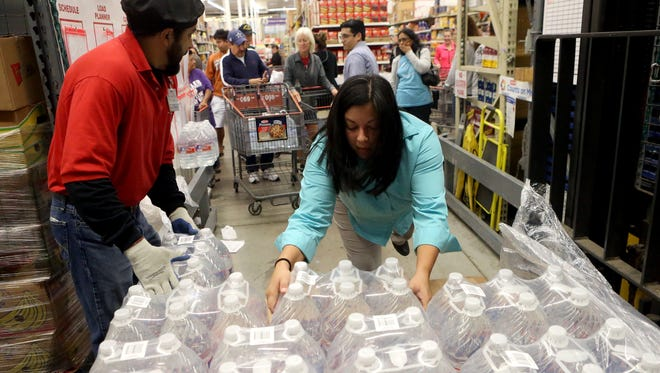 H-E-B employees remove bottles of water from a crate to hand out to customers after City of Corpus Christi officials confirmed Thursday morning that one chemical contaminated the cityÕs water supply on Thursday, Dec. 15, 2016, at H-E-B store in Corpus Christi.