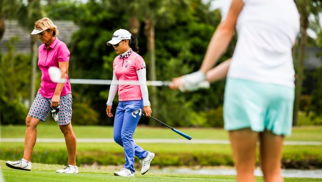 Barb Mucha of Orlando, Florida, walks with Sue Kim, Langley, British Columbia, up to the green on hole 17 as Katherine Perry, Carry, N.C., prepares to hit.  2016 Chico's Patty Berg Memorial Round 3 Saturday, April 16, 2016 at Cypress Lake Country Club.