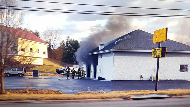 Firefighters are seen Wednesday morning putting out a fire at the Xpress Lube in Waynesboro.