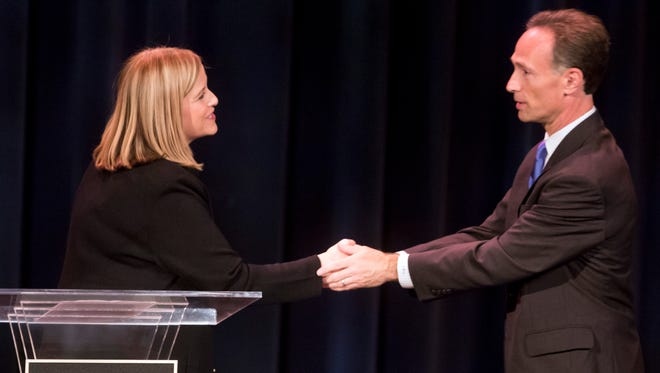 Mayoral candidates Megan Barry and David Fox shake hands following a debate held at the Blair School of Music on Vanderbilt's campus Monday.