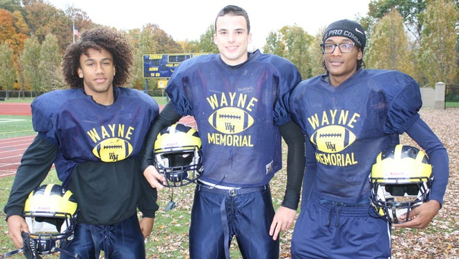 Wayne Memorial senior receivers Angelo Wiggins (left) and Juan Wise flank junior quarterback Joe Bob Walker. All three players were instrumental in the Zebras'  47-28 victory over South Lyon East on Oct. 17. The win was the school's first since Oct. 2, 2009.