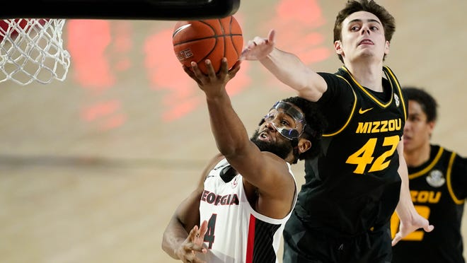 Georgia forward Andrew Garcia (4) shoots as Missouri forward Parker Braun (42) defends during a game in February.