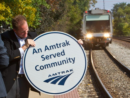 State Rep. Randy Truitt holds a sign that calls Lafayette an Amtrak-served community.