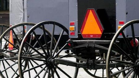 Amish buggies are shown using the standard warning symbol of a bright orange triangle required by state law on slow-moving vehicles
