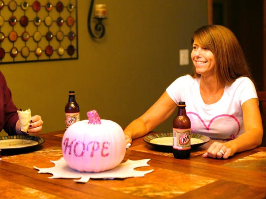 Breast cancer survivor Jen Mahoney, right, and her daughter Joselyn Gruenke share a laugh during dinner Thursday at the family's Green Bay residence. Mahoney had a double mastectomy and is cancer-free.