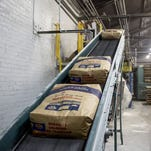 Bags of sugar travel along a conveyor belt in August 2016 at the Michigan Sugar plant in Croswell.