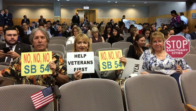 Opponents of sanctuary cities show signs at a California Senate hearing earlier this year in Sacramento.