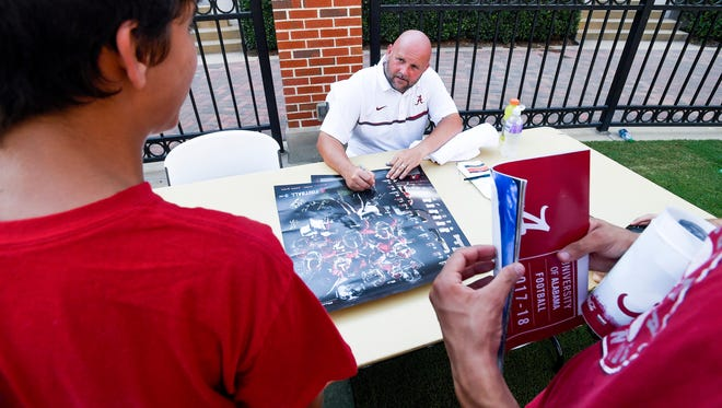 Alabama offensive coordinator Brian Daboll signs autographs during fan day in Tuscaloosa, Ala. on Saturday August 5, 2017.