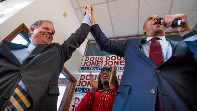 Democratic U.S. Senate candidate Doug Jones, left, U.S. Rep. Terri Sewell, center, and U.S. Sen Cory Booker, right, during a rally at Jones' campaign headquarters in Birmingham, Ala. on Sunday December 10, 2017.