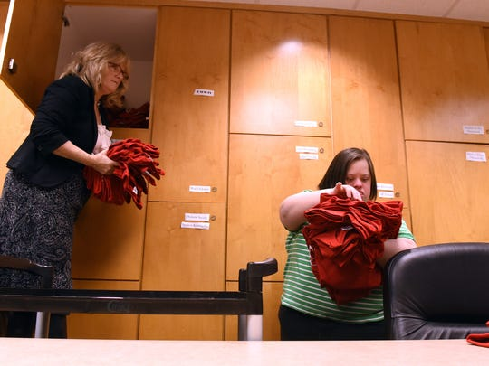 Associate director for the Alford Center Susie Kalinoski gets out volunteer t-shirts as Sarah Burkett organizes the shirts by size for an upcoming event while working at Denison University in Granville. Sarah works for the Campus Leadership and Involvement Center at Denison.